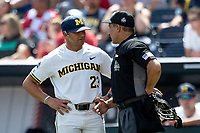 Michigan Wolverines Head Coach Erik Bakich (23) talks with home plate umpire Perry Costello during Game 1 of the NCAA College World Series against the Texas Tech Red Raiders on June 15, 2019 at TD Ameritrade Park in Omaha, Nebraska. Michigan defeated Texas Tech 5-3. (Andrew Woolley/Four Seam Images)