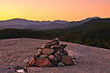 A lonely cairn mimics distant mountains at sunset.