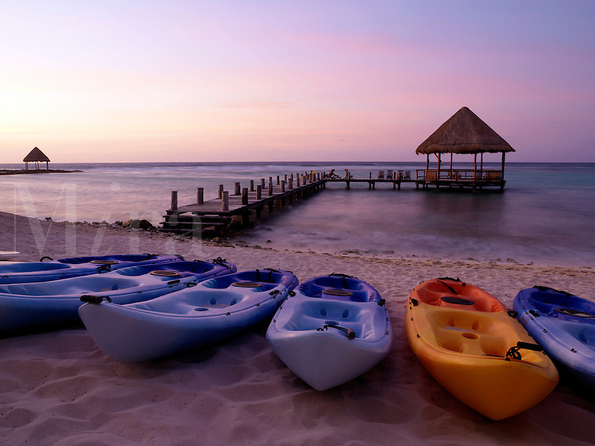 Mexico Quintana Roo Yucatan Peninsula Akumal Mayan Riviera pier with palapa jutting out to the water from the beach with kayaks lined on shore of beach at dawn