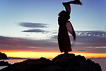 Artistic dynamic photograph of a woman back dark silhouette in long red dress dancing on the rocks of an ocean shore in the wind in sunset sky scenery Image © MaximImages, License at https://www.maximimages.com