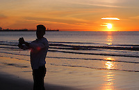 WEATHER PICTURE WALES<br /> Pictured: A young man takes a selfie while the sun rises over Swansea Bay in Wales, UK. Wednesday 30 November 2016<br /> Re: Low temperatures with sunshine in most parts of the UK
