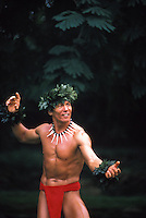 Hawaiian warrior hula dancer in red loin cloth with green leaf leis on head and wrist