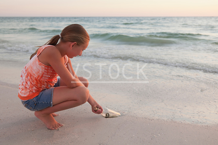 USA, Florida, St. Petersburg, Girl (10-11) reaching for bottle with money on beach