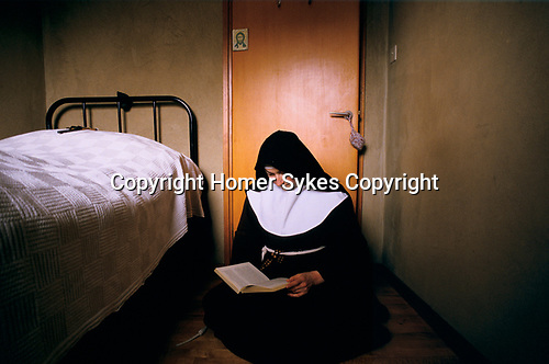 Much Birch, Herefordshire. 1989<br /> Colettine Poor Clares are an enclosed Catholic order that observe night rising, perpetual fast and the observance of papal enclosure. They go barefoot as a sign of Gospel poverty and in witness to the transcendence of God. Sister Colette reads her bible in her cell. A soft doorstop hangs around the handle to prevent it shutting noisily. On the bed she has placed a crucifix, the image of Christ on the door is positioned at eye level, which she would look at before pulling back the bed covers at night.