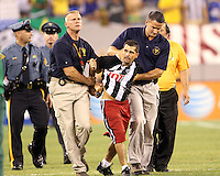 Police escort a field invader off the field during an international friendly match between the USA and Brazil in Giants Stadium, on August 10 2010, in East Rutherford, New Jersey.Brazil won 2-0.