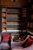 A corner of a study with a collection of books in rows in a wooden bookcase. Two armchairs provide a quiet spot for sitting and reading