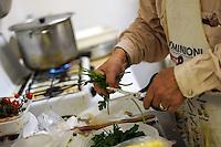 Vecchi amici. Old friends..Nello storico quartiere di San Lorenzo a Roma, un gruppo di amici si riunisce per pranzo,nella falegnameria di Graziano Azzurri.L' occasione è il compleanno di Vincenzo, 76 anni ex tassista..In the historic district of  San Lorenzo in Rome, a group of friends meets for lunch, in carpentry of Graziano Azzurri. On the occasion of the birthday of  Vincenzo, 76 years ex taxi driver..Alberto Manzoni,cantante romano,mentre cucina. Alberto Manzoni, Roman singer, while cooking....
