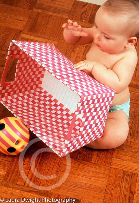 10 month old baby girl turning over basket to find hidden toy Piaget object permanence vertical Caucasian