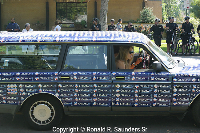 Two young women show their support for candidate Obama by covering stickers on the hood of their car during the 2008 Democratic Convention.(3)