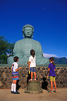 Three children look up at the Buddha statue at the Lahaina Jodo Mission.