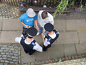 Police inspect a bag they suspect contains marijuana after detaining two young men in Camden Town, London