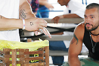Richard Calero looks on as a fellow arm wrestler chalks himself up at the Staten Island Borough Championship on June 18, 2005.