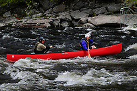 Two canoeists paddling on the Hudson River competing in the Hudson River White Water Derby in the  Adirondack Forest Preserve in New York