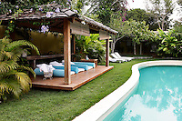 Covered outdoor lounge area with cushions by swimming pool