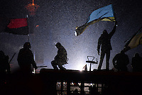 A  protester waves an Ukrainian flag on top of a barricade under the snow during the protest against new draconian law to ban protests across the country.  Kiev. Ukraine