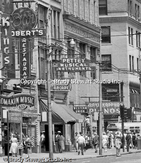 Pittsburgh PA:  View east on Liberty Avenue toward Pennsylvania Railroad Station.  Businesses on the north side (600 block) of the street include Kings Clothing Store, Lomakin Music, Robert's Restaurant & Bar, Pettey Musical Instruments, Ace Amusement, and Arcade, and Western Union.