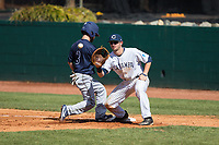Ty Andrus (3) of the Wingate Bulldogs gets back safely to first base as Chance Bowden (15) of the Catawba Indians waits for a pick-off throw at Newman Park on March 19, 2017 in Salisbury, North Carolina. The Indians defeated the Bulldogs 12-6. (Brian Westerholt/Four Seam Images)