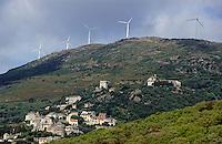 Wind turbines on a mountain top above Rogliano Village, Corsica Island, France.