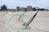 Nederland - Amsterdam - 2021. Op het nieuw aangelegde Centrumeiland worden huizen gebouwd naar eigen ontwerp. Het wordt een van de duurzaamste ontwikkellocaties van de stad. Bouwgrond met kabels. Foto ANP / Hollandse Hoogte / Berlinda van Dam