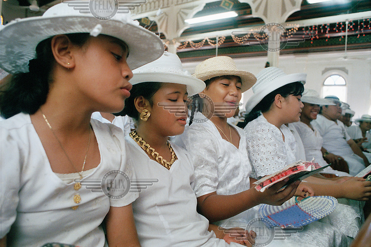 Young girls wearing white hats and dresses read the bible in church during one of the many services leading up to Christmas and through to the New Year.