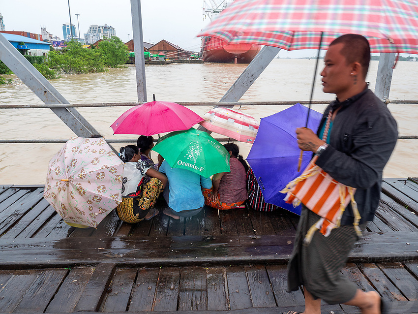 Relatives waiting in the Monsoon rain for news from their loved ones at the spot where a boat sunk the day before along the Yangon River, Yangon, Myanmar.