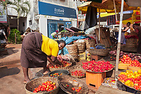 Nigeria. Enugu State. Enugu. Ogbete main market is the biggest commodity market. Vegetable market stall. A woman cleans with water tomatoes in order to sell them better. In the background, the entrance to Ecobank, whose official name is Ecobank Transnational Inc. (ETI), which is a pan-African banking conglomerate, with banking operations in 36 African countries. It is the leading independent regional banking group in West Africa and Central Africa, serving wholesale and retail customers. Cash machine. A sign for MoneyGram International Inc. which is a money transfer company. The company provides its service to individuals and businesses through a network of agents and financial institutions around the world. Ogbete main market is the choice market for wholesale buyers and sellers.  Residents of Enugu usually prefer going to Ogbete for major shopping, to buy things in bulk, to purchase quality and original goods, to have access to varieties, to buy new products and to buy goods at wholesale or company price. Apart from clothing and textile materials, prices of commodities in the market are moderately cheap. Enugu is the capital of Enugu State, located in southeastern Nigeria. 13.07.19 © 2019 Didier Ruef