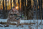 Crossbow hunter sitting on a log