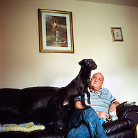 Tommy and his dog Alex at his home in UpperArdoyne, Belfast.