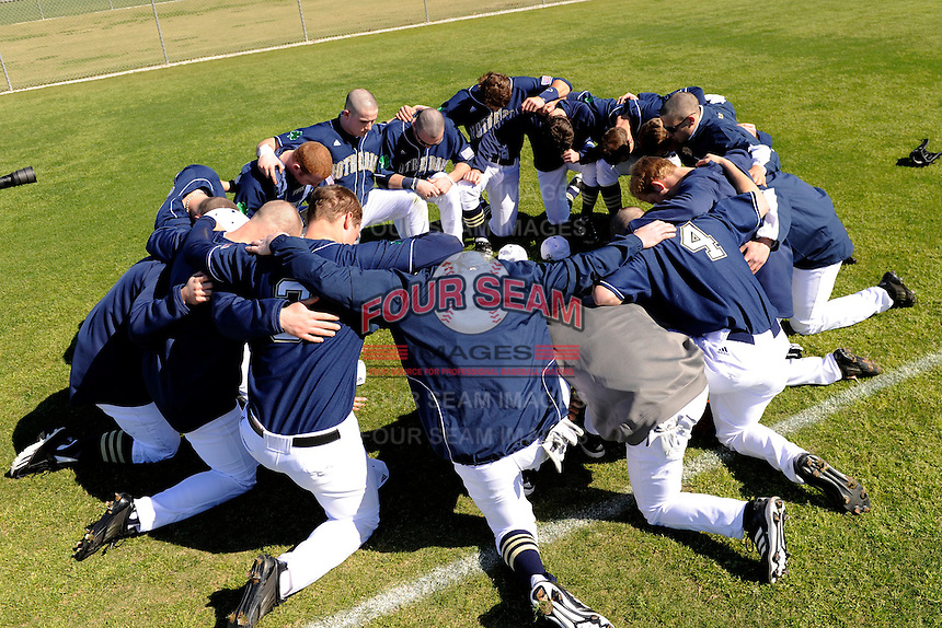 Notre Dame Fighting Irish players pray before a game against the Mercer Bears at the Buck O'Neil Complex on February 17, 2013 in Sarasota, Florida.  Mercer defeated Notre Dame 5-4.  (Mike Janes/Four Seam Images)