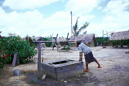 Ipixuna village, Amazon, Brazil. Arawete nurse inspecting the well in the village.
