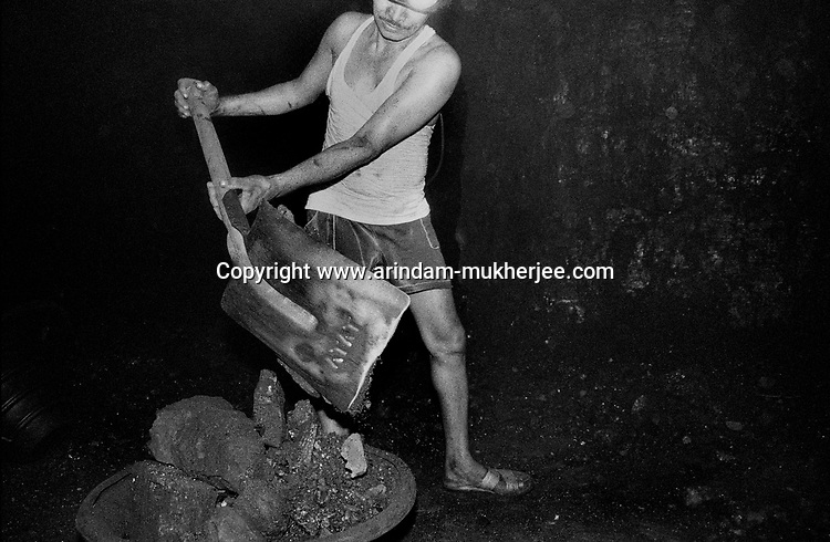 A worker using a shovel to fill a bucket inside an underground mine at North Searsole Coliery in Ranigunj, West Bengal, India. Arindam Mukherjee