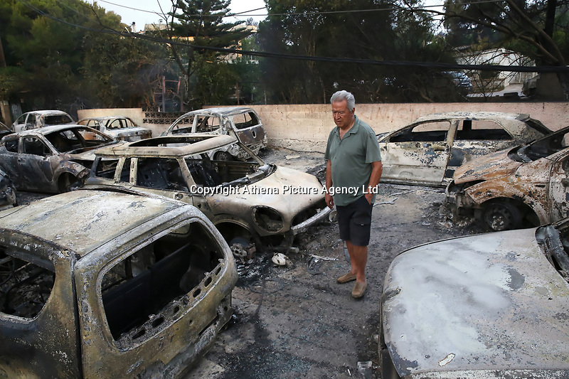 Pictured: A local man walks in despair amongst the burned cars in the Mati area, Kokkino Limanaki near Rafina, Greece. Tuesday 24 July 2018<br /> Re: Deaths caused by wild forest fires throughout Greece.
