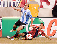 Landon Donovan (10) of the United States tackles the ball away from Javier Mascherano (14) of Argentina during an international friendly at New Meadowlands Stadium in East Rutherford, NJ.  The United States tied Argentina, 1-1.