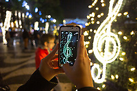 Lisbon, Portugal - December 23: A person takes a picture with her phone at a Christmas tree  near Comercio square in downtown Lisbon, Portugal December 23, 2019. <br /> The Christmas lights in Lisbon are getting more sophisticated and stunning each time, they are an attraction to locals and tourists to choose Lisbon as a place to spend the holidays<br /> (Photo by Luis Boza/VIEWpress/Corbis via Getty Images)