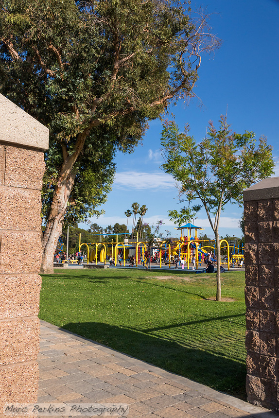 A vertically-cropped view of one of the entrances to South Gate Park: block columns frame a paver pathway that curves under mature trees while leading to a giant playground full of children.