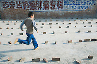 China. Province of Henan. Village Xiaotan. A young boy runs among bricks laid on the ground. © 2004 Didier Ruef