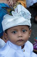 Bali, Indonesia.  Little Hindu Boy Wearing an Udeng, the Traditional Balinese Male Head Wrap.  Pura Dalem Temple.  Dlod Blungbang Village.