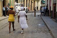 Women walking down a city street together near Plaza Vieja, Havana, Cuba.