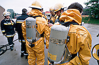 Firefighters donning breathing apparatus and chemical protection suits before entering a chemical spillage in a large factory. This image may only be used to portray the subject in a positive manner..©shoutpictures.com..john@shoutpictures.com