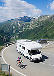 Switzerland, Canton Valais, Camper and cyclist at Furka Pass Road, Grimsel Pass Road in the Background