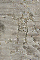 Petroglyph, rock carving, of a warrior holding swords and shields. Carved by the ancient Camuni people in the iron age between 1000-1600 BC. Rock no 24,  Foppi di Nadro, Riserva Naturale Incisioni Rupestri di Ceto, Cimbergo e Paspardo, Capo di Ponti, Valcamonica (Val Camonica), Lombardy plain, Italy
