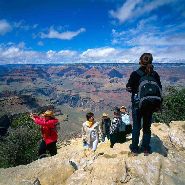 Grand Canyon National Park, Arizona, USA - Tourists standing at Cliff Edge and taking Pictures of Scenic View from South Rim, overlooking Grand Canyon and North Rim