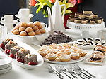 A buffet table with a large assortment of fancy desserts