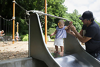 Francisco Samayoa of Bentonville (right) helps Nicole Samayoa, 1, ride down a slide, Sunday, July 18, 2021 at the playground at Lake Atalanta. Check out nwaonline.com/210719Daily/ for today's photo gallery. <br /> (NWA Democrat-Gazette/Charlie Kaijo)