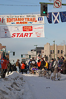 Musher Nicolas Petit and Iditarider Linda Chowns.leave the 2011 Iditarod ceremonial start line in downtown Anchorage, Alaska