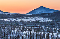 The trans Alaska oil pipeline traverses the Arctic winter tundra and boreal forest of the foothills of the Brooks Range mountains.