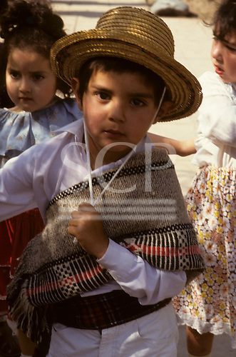Santiago, Chile. Young boy in traditional dress wearing a straw hat at a festival.