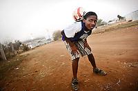 Un ragazzo che vive nelle case del villaggio di Sun City a 200 metri dal Royal Bafokeng Stadium di Rustenburg gioca a pallone sulla strada con alle spalle lo stadio.USA Ghana 1-2 - USA vs Ghana 1-2.Ottavi di finale - Round of 16 matches.Campionati del Mondo di Calcio Sudafrica 2010 - World Cup South Africa 2010.Royal Bafokeng Stadium, Rustenburg, 26 / 06 / 2010.© Giorgio Perottino / Insidefoto .