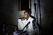 66-year-old Manganiyar artist, Lakha Khan listens to the field recording of his Sarangi in the dark in Raneri village of Jodhpur district in Rajasthan, India. Photo: Sanjit Das/Panos