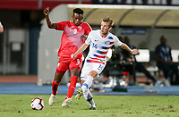 GEORGETOWN, GRAND CAYMAN, CAYMAN ISLANDS - NOVEMBER 19: Jackson Yueill #14 of the United States passes off the ball past Maykel Reyes #9 of Cuba during a game between Cuba and USMNT at Truman Bodden Sports Complex on November 19, 2019 in Georgetown, Grand Cayman.